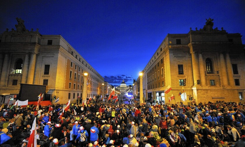 People are gathered on the Via della Conciliazione, which leads to St. Peter's Square on the eve of the canonization of Pope John Paul II and Pope John XXIII.
