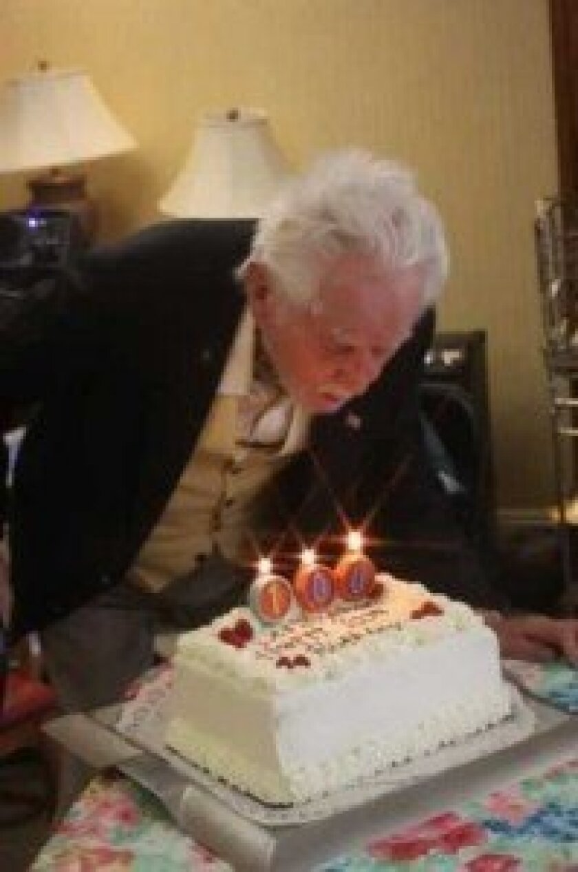 Stypinski blows out the candles on his 100th birthday cake.