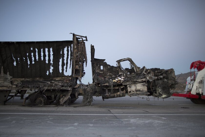 The scorched remains of a truck are towed at the North Fire, which caused people to abandon their vehicles and flee as flames jumped the 215 freeway on July 17, near Victorville, California. The fire has burned across 3,500 acres and a private drone was reported to have raised serious safety concerns for aircraft pilots fighting the fire.