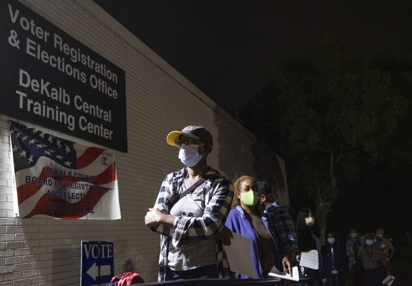 Voters wait in line before early balloting begins in Decatur, Ga., on Oct. 12.