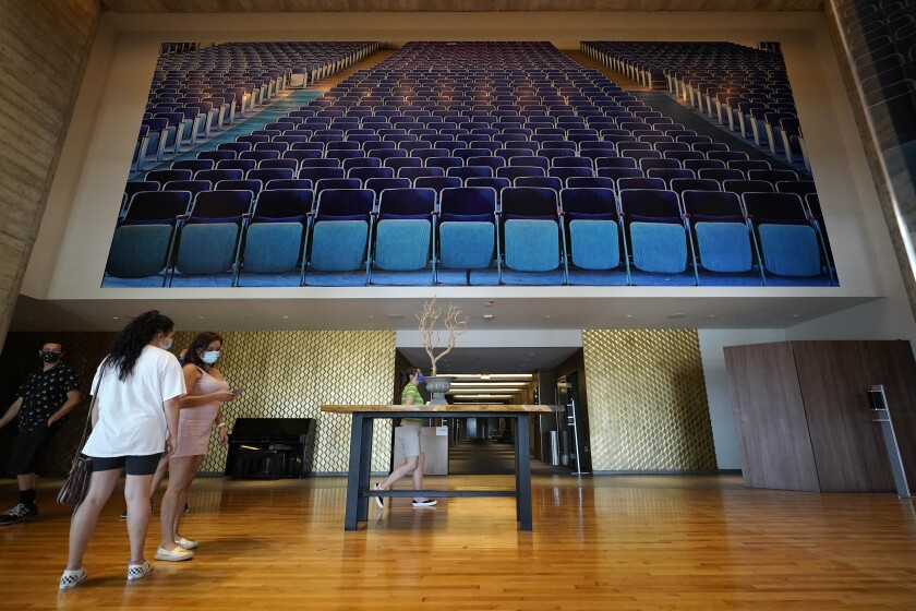 FILE - In this Sept. 3, 2020, file photo, people wait for their movie in the lobby of The Lot in San Diego. California's coronavirus infection rate has reached its lowest level since earlier days in the pandemic but San Diego County, the state's second-largest, is seeing an uptick in cases that could shut down some recently reopened businesses. (AP Photo/Gregory Bull)