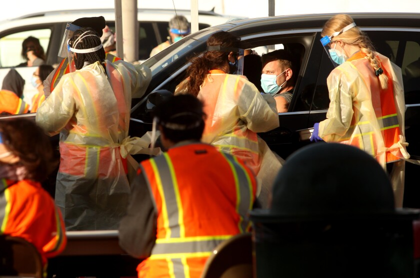 Medical workers tend to people waiting in their cars at a COVID-19 vaccine site at Cal State Northridge on Tuesday.