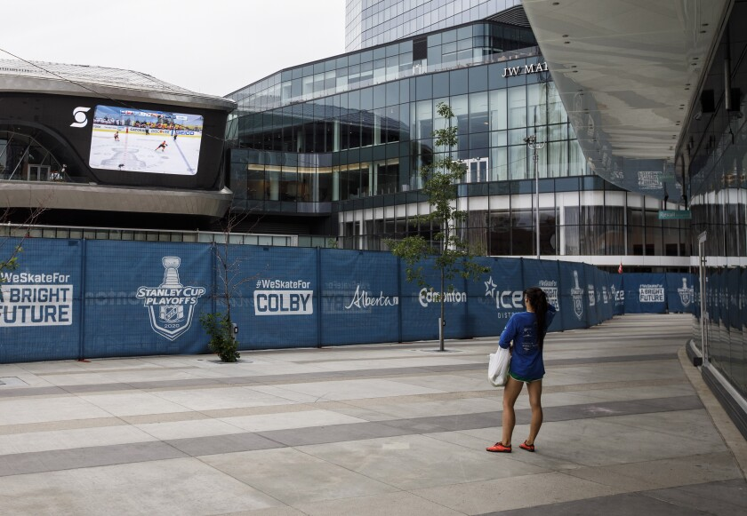FILE - A woman watches a hockey game on the big screen just outside the bubble at the NHL Western Conference Stanley Cup hockey playoffs in Edmonton, Alberta, on Monday, Aug. 24, 2020. (Jason Franson/The Canadian Press via AP)