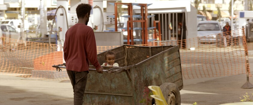 """A man pushes a small child in a cart in the movie """"Running Against the Wind."""""""
