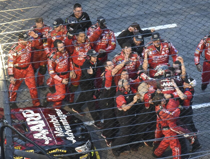 Jeff Gordon (wearing helmet), right, celebrates afte winning the NASCAR Sprint Cup Series auto race with his team at Martinsville Speedway in Martinsville, Va., Sunday, Nov. 1, 2015. (AP Photo/Don Petersen)