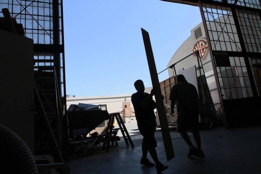 Warner Bros. purchased $3.4 million worth of construction supplies and $2.4 million worth of food and catering services from Burbank vendors in 2010. Above, a worker carries lumber at the studio.