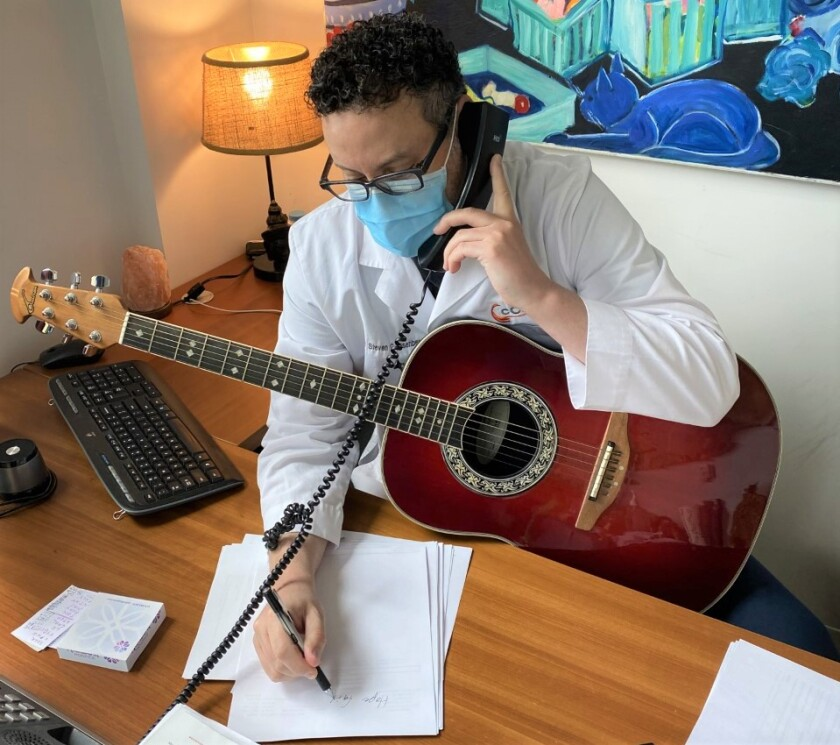 Dr. Steven Eisenberg holds a guitar while taking patient notes on the phone. He writes songs with them as part of treatment.