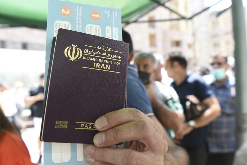 A person holds up an Iranian passport as people, most of them residents of Iran stand in line for a vaccine at a mobile vaccination station in the center of Yerevan , Armenia, Friday, July 9, 2021. Armenia's offer of free coronavirus vaccines to any foreign visitor has drawn many people from neighboring Iran and other countries to the ex-Soviet Caucasus nation. The Iranians initially visited the Armenian border city of Meghri to get the shots, but the Armenian authorities have decided earlier this week that all foreign nationals should get the shots in the Armenian capital, Yerevan. (Lusi Sargsyan/PHOTOLURE via AP)