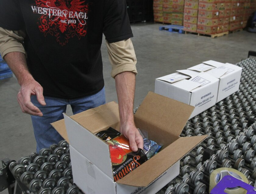 Steve Johnson, a warehouse manager at Western Eagle food bank in Temecula, unpacks one of the seafood boxes offered since the company paired with Golden Share Foods.