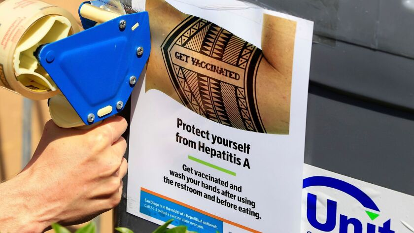 A worker in downtown San Diego tapes up a sign telling people to get vaccinated to protect themselves against hepatitis A.