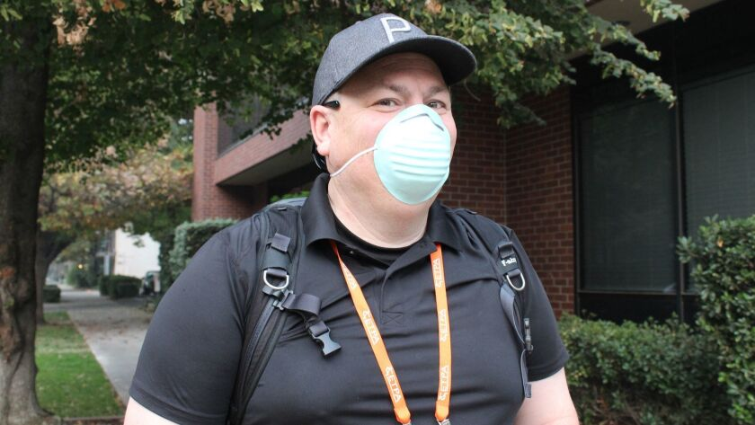 Toby Lewsadder of Los Angeles wears a dust mask while visiting Sacramento because that was all he could find at a local hardware store.