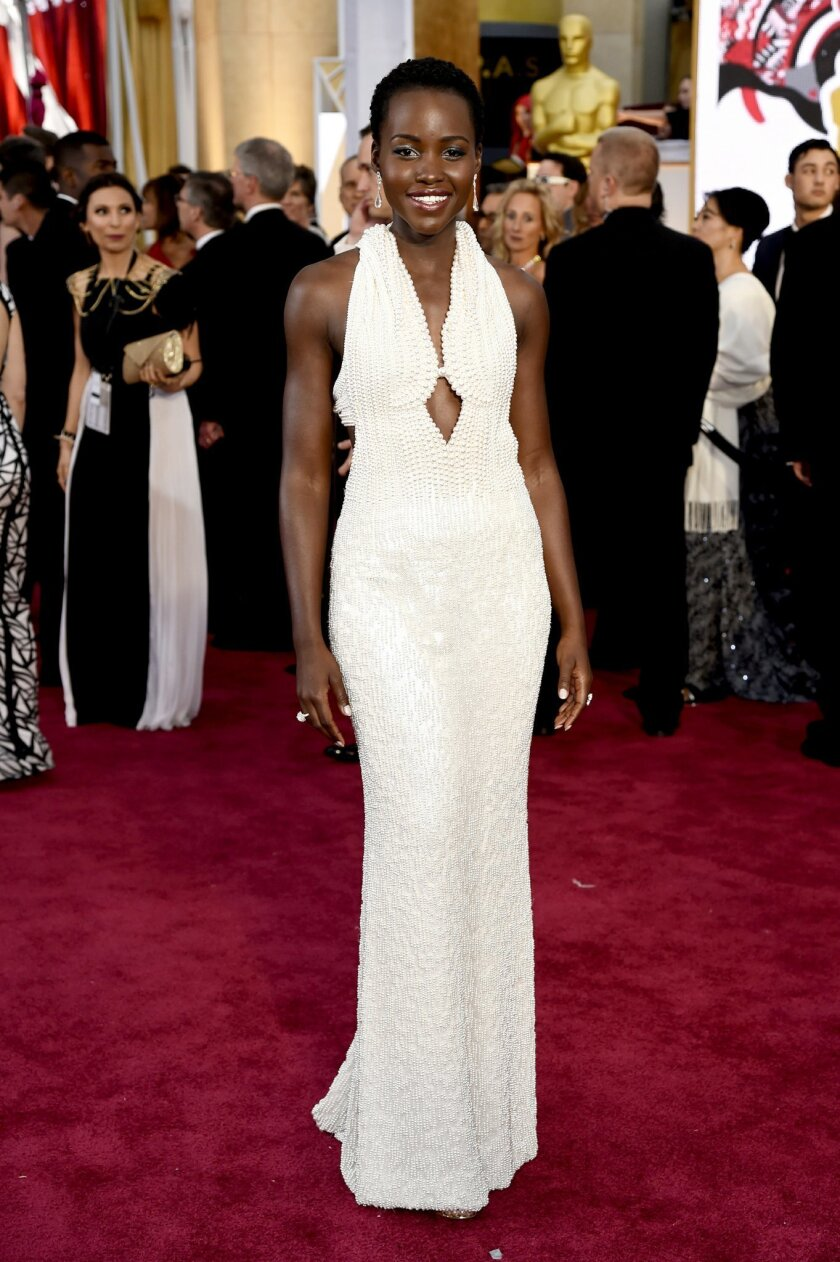 FILE - In this Feb. 22, 2015 file photo, actress Lupita Nyong'o arrives at the Oscars wearing a dress made of pearls at the Dolby Theatre in Los Angeles. Los Angeles sheriff's detectives are investigating the theft of the $150,000 custom Calvin Klein dress worn by Nyong'o at the 2015 Academy Awards. The dress was reported stolen from Nyong'o's West Hollywood hotel room late on Wednesday Feb. 25, 2015. (Photo by Chris Pizzello/Invision/AP, File)