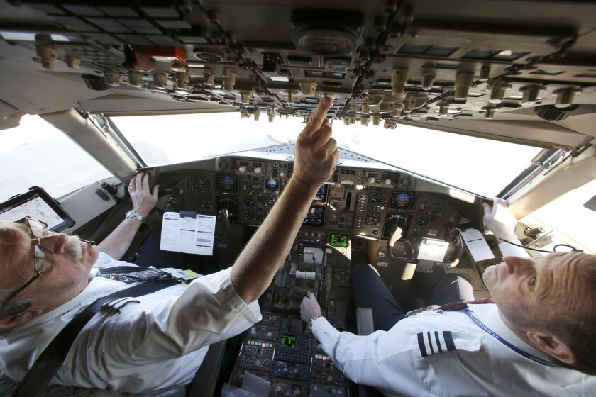Capt. Paul Wannberg, left, and First Officer Robert Popp prepare a Boeing 757 jet for takeoff from Dallas/Fort Worth International Airport. Signs of a pilot shortage are mixed.