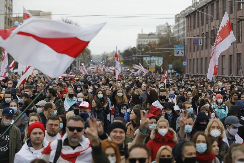 Una multitud de opositores marcha con antiguas banderas bielorrusas en protesta por los resultados de las elecciones presidenciales, el domingo 25 de octubre de 2020, en Minsk, Bielorrusia. (AP Foto)