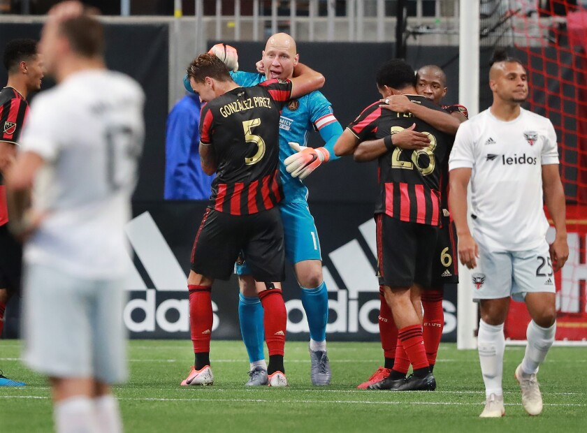 Atlanta United goalkeeper Brad Guzan, defender Leandro Gonzalez Pirez (from left), Dion Pereira and Darlington Nagbe celebrate a 2-0 victory over D.C. United while Quincey Amarikwa walks away dejected as time expires on Sunday, July 21, 2019, in Atlanta, Ga. (Curtis Compton/Atlanta Journal-Constitution/TNS) ** OUTS - ELSENT, FPG, TCN - OUTS **