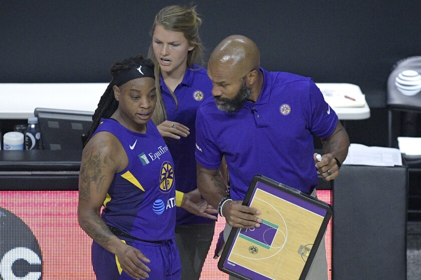 Sparks guard Riquna Williams talks strategy with coach Derek Fisher during a game against the Fever on Saturday.