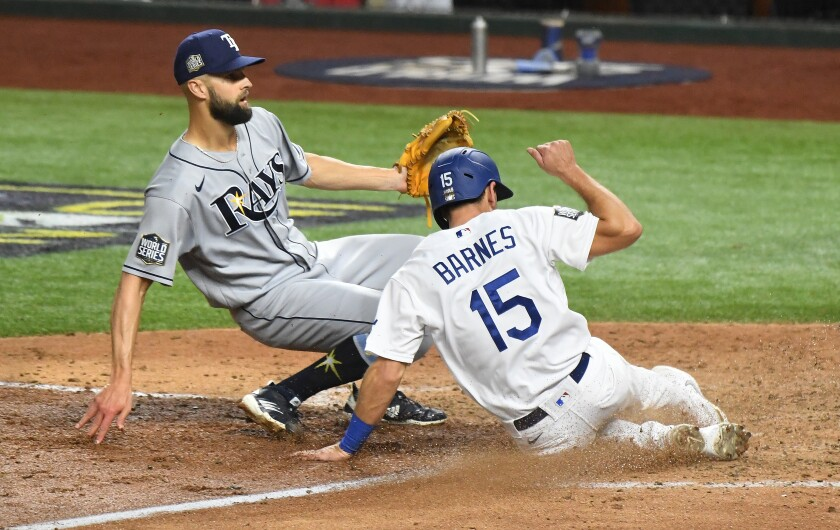 Dodgers catcher Austin Barnes scores in front of Tampa Bay Rays pitcher Nick Anderson on a wild pitch.