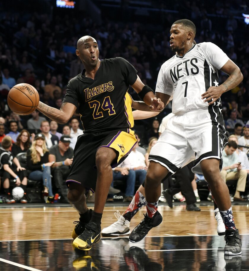 Los Angeles Lakers forward Kobe Bryant (24) passes the ball around Brooklyn Nets forward Joe Johnson (7) during the first half of an NBA basketball game Friday, Nov. 6, 2015, in New York. (AP Photo/Kathy Kmonicek)