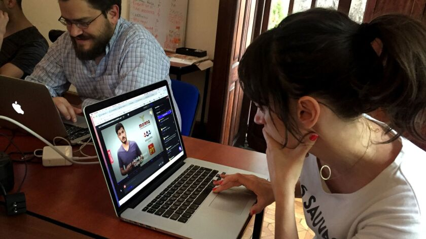 Alba Mora Roca, right, a journalist with Verificado 18, works on a video at the group's Mexico City