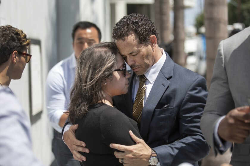 Pilar Looney, left, and Benson Williams comfort each other at a news conference Thursday outside the Orange County district attorney's office. A Fullerton police officer fatally shot their daughter Hannah Williams, 17, last week on the 91 Freeway.