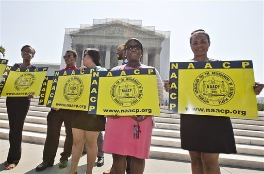 Representatives from the NAACP Legal Defense Fund stand outside the Supreme Court in Washington, Tuesday, June 25, 2013, awaiting a decision in Shelby County v. Holder, a voting rights case in Alabama.