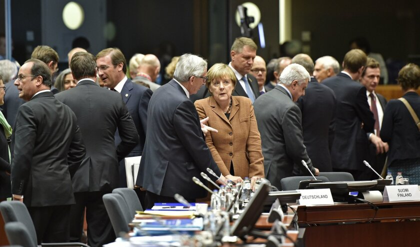 German Chancellor Angela Merkel, center right, listens to European Commission President Jean-Claude Juncker , center left, as they arrive for an emergency EU heads of state summit on the migrant crisis at the EU Commission headquarters in Brussels on Wednesday, Sept. 23, 2015. (AP Photo/Martin Meissner)