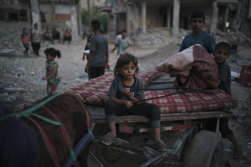 Chadi Nassir, de 7 siete años, se sienta en un carro tirado por un burro mientras su hermano, Mahmoud, lo carga con pertenencias recuperadas de su casa dañada en Beit Hanoun, en el norte de la Franja de Gaza, el domingo 13 de junio de 2021. (AP Foto/Felipe Dana)