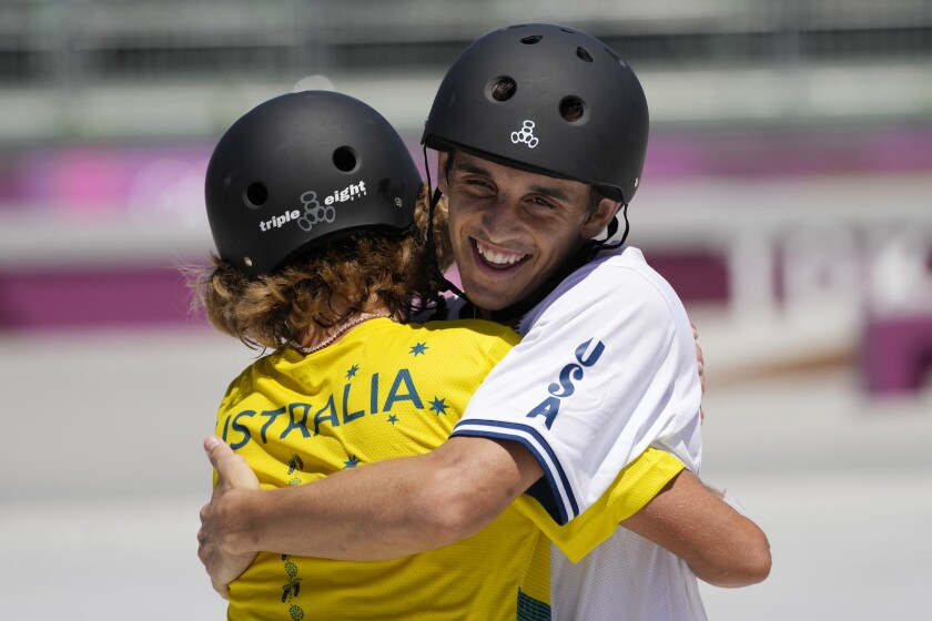 Two skateboard athletes embrace at the Olympics