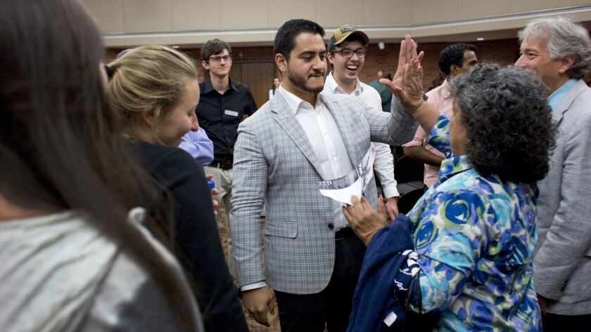 Michigan governor candidate Dr. Abdul El-Sayed gives a high-five to a woman in the crowd after a tow