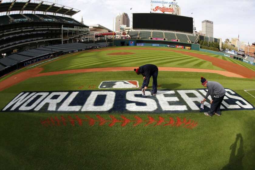 John Dileo, right, and Mathew Gudin of the Progressive Field ground crew paint touch up the World Series logo along the first baseline Monday, Oct. 31, 2016 in preparation for Tuesday night's game six of the World Series between the Cleveland Indians and Chicago Cubs in Cleveland. (AP Photo/Gene J. Puskar)