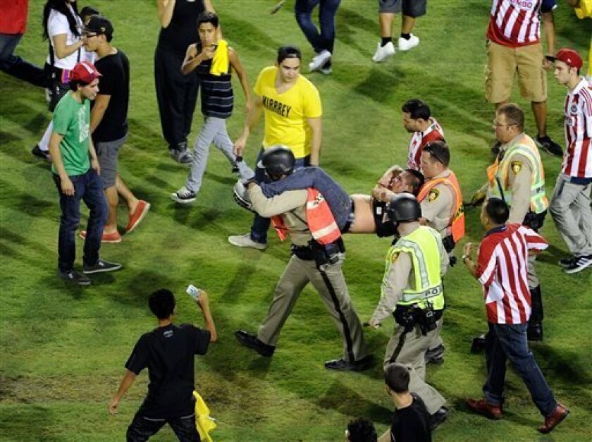 Police carry off a fan from the field after after Chivas defeated Club America 1-0 at the El Super Clasico soccer match on Wednesday, July 3, 2013 in Las Vegas. (AP Photo/David Becker)