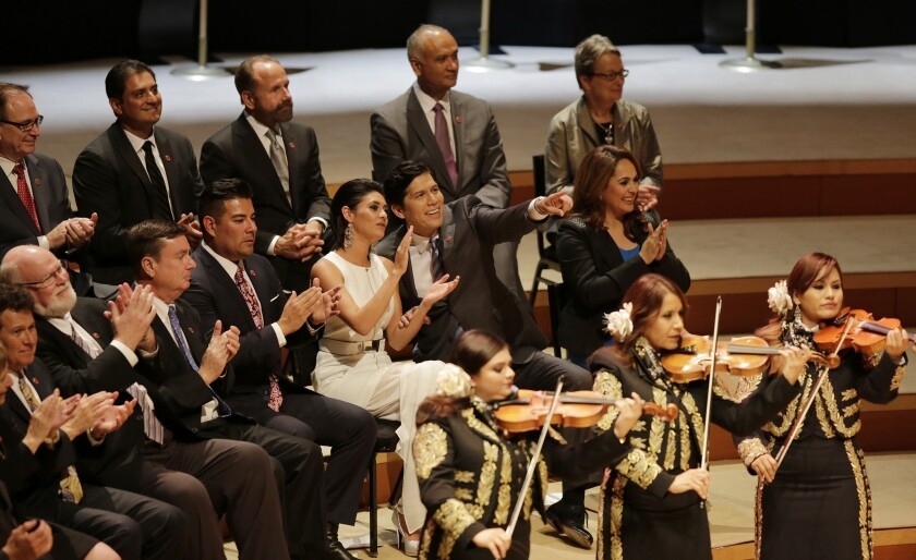 As the Mariachi Divas play, Kevin de León, with his daughter Lluvia Carrasco, points to friends in the crowd at his swearing-in ceremony.