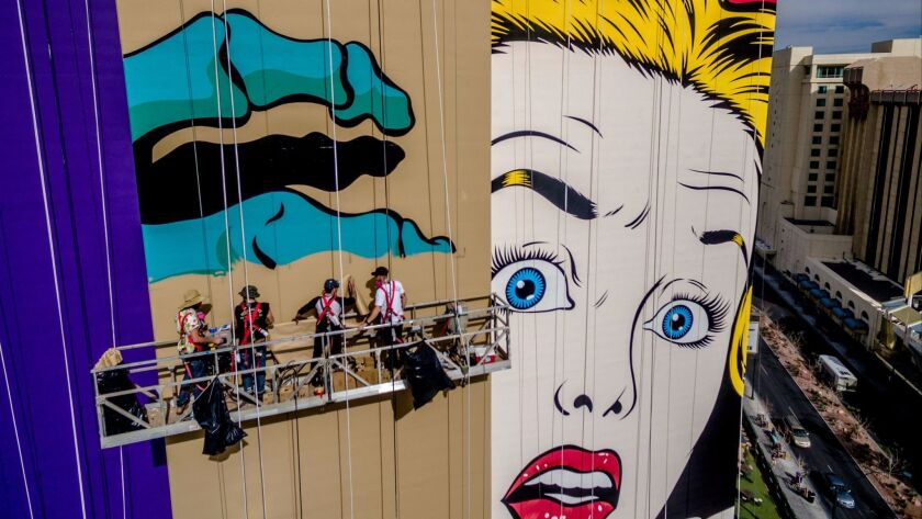 """On a scaffold high above downtown Las Vegas, British muralist D*Face and artists from JustKids put the finishing touches on """"Behind Closed Doors,"""" a mural on the north tower of the Plaza Hotel & Casino."""