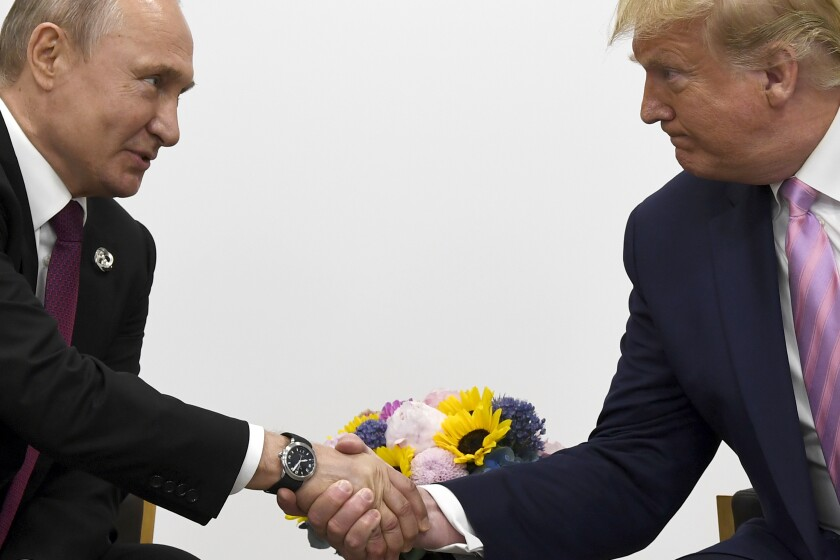 """FILE - In this file photo taken on Friday, June 28, 2019, President Donald Trump, right, shakes hands with Russian President Vladimir Putin during a bilateral meeting on the sidelines of the G-20 summit in Osaka, Japan. From Moscow, the U.S. election looks like a contest between """"who dislikes Russia most,"""" according to Kremlin spokesman Dmitry Peskov. Russian President Vladimir Putin is frustrated with President Donald Trump's failure to deliver on his promise to fix ties between the countries. But Democratic challenger Joe Biden does not offer the Kremlin much hope either. (AP Photo/Susan Walsh, File)"""