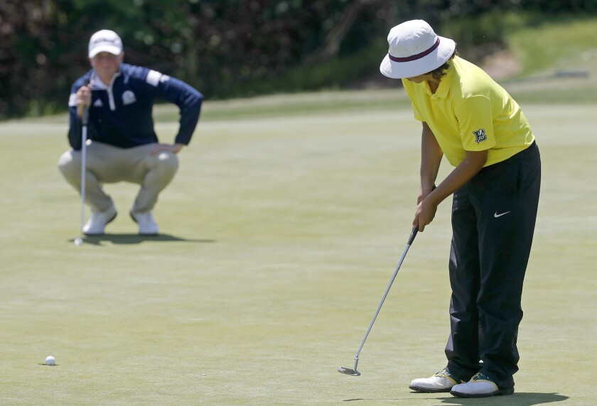 Edison High's Tiger Tahvildari putts the ball in at hole No. 14 in the CIF Southern Section Southern
