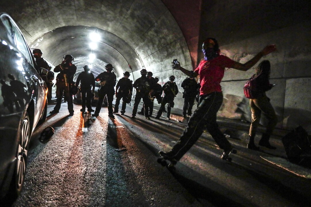 Liliana Ruiz roller skates in front of LAPD officers in the 3rd Street Tunnel.