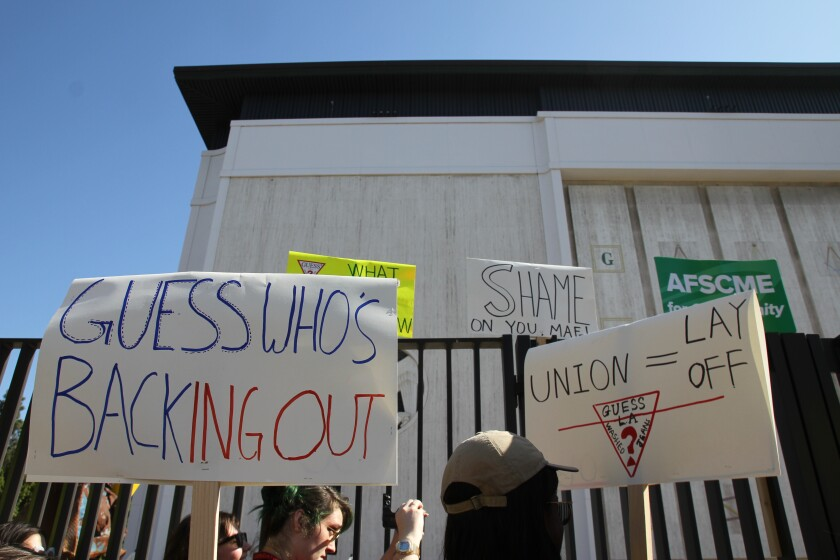 "Workers protest outside the Marciano Art Foundation in 2019 with a sign that reads: ""Guess who's Backing Out?"""