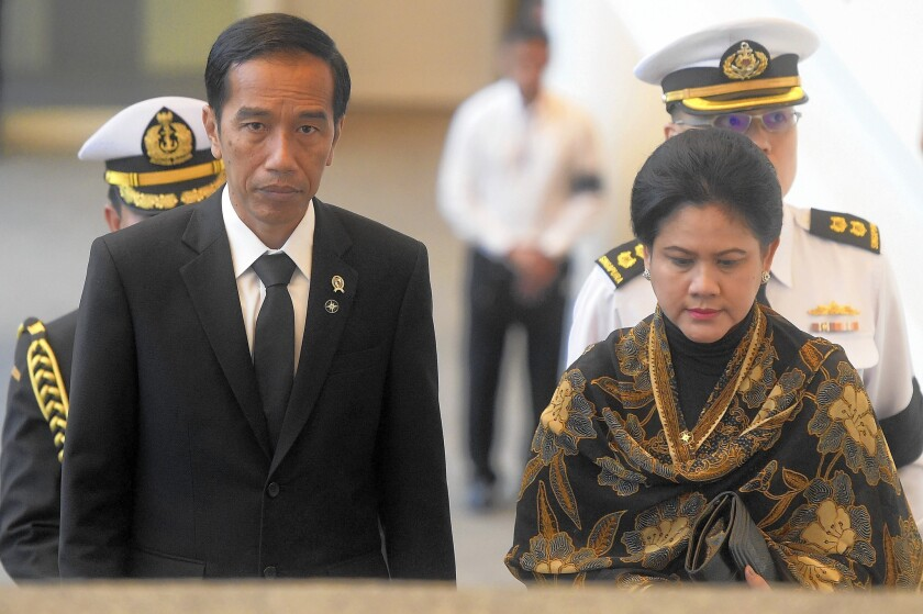 President Joko Widodo, seen here with his wife, Iriana Joko Widodo, has gotten some praise along with the criticism, and an analyst noted that his election may have generated unrealistic expectations.
