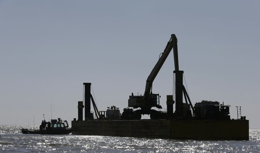 Barges holding a large excavator and piles of limestone boulders are silhouetted in the gulf of Mexico off the Texas coast on Tuesday, Oct. 29, 2013. The huge boulders will be dropped into the water to help rebuild a reef that once filled some 400 acres and now barely exists. (AP Photo/Pat Sullivan