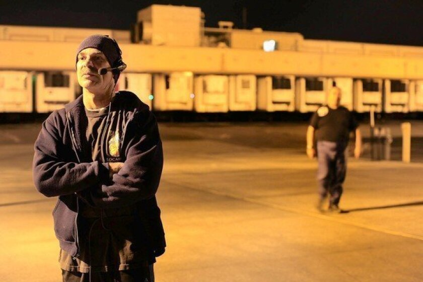 """Phil Richards, who drives a forklift at a warehouse in Santa Fe Springs, is required to wear a headset through which he is told what to do and how quickly he must do it. """"We're just like human machines,"""" he says."""