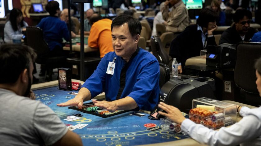 La Nam deals blackjack poker at the Gardens Casino in Hawaiian Gardens on Nov 27. State regulators are considering adopting new regulations for the third-party banker, seated left of Nam. The players bet against the banker not the dealer.
