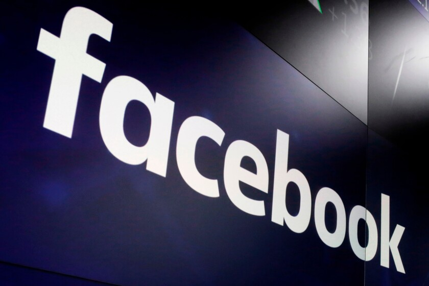 """FILE- In this March 29, 2018, file photo, the logo for Facebook appears on screens at the Nasdaq MarketSite in New York's Times Square. Facebook's recommendation algorithm amplifies military propaganda and other material that breaches the company's own policies in Myanmar even though the social media giant says it's treating the situation there as an emergency following February's military coup, a new report by the rights group Global Witness has found. A month after the military seized power in Myanmar and imprisoned elected leaders, Facebook's algorithms were still prompting users to view and """"like"""" pro-military pages with posts that incited and threatened violence, pushed misinformation that could lead to physical harm, praised the military and glorified its abuses, Global Witness said in the report, published late Tuesday, June 22, 2021. (AP Photo/Richard Drew, File)"""