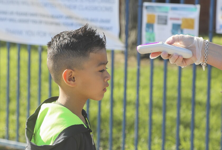 Max Lucatero, 7, has his temperature taken by Natalie Perez before entering Chase Avenue Elementary School during the Cajon Valley Union School District's Emergency Child Care Program on May 5 in El Cajon. In order to reopen, some school districts anticipate needing more nurses to conduct health checks of students and staff.