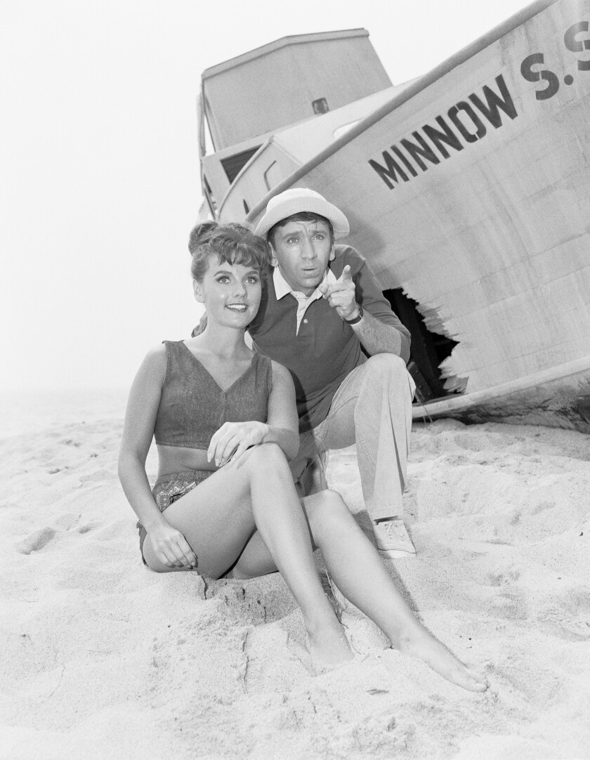 """Dawn Wells and Bob Denver in the sand next to the S.S. Minnow on """"Gilligan's Island."""""""