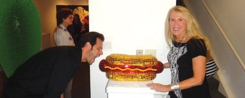 """Rancho Santa Fe artist Jean Wells' hot dog is currently on display in the Frederick R. Weisman Museum of Art's """"Pop Culture"""" exhibit. She is seen here with fellow artist Robert Townsend pretending to take a bite."""