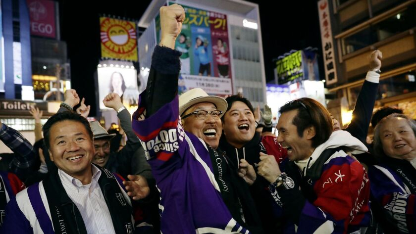 People in Osaka, western Japan celebrate Saturday Nov. 24, 2018 after winning the vote at the 164th