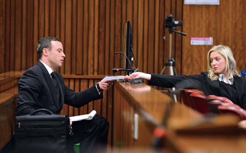 Oscar Pistorius hands a note to a member of his legal team at the High Court in Pretoria, South Africa.