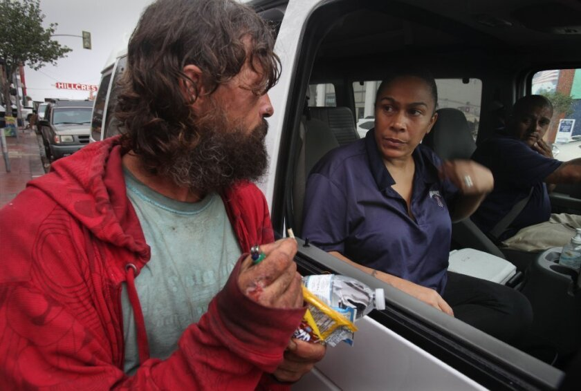 Chuck Goins accepts water and snacks from Alpha Project outreach team members Larissa Wimberly and Carlos Juarez on a recent drizzly morning in Hillcrest. The Hillcrest Business Association has contracted with the Alpha Project for the team to target the homeless that loiter outside businesses in that area.