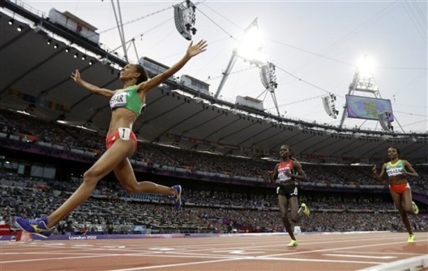 Ethiopia's Meseret Defar, left, reacts as she crosses the finish line to win gold ahead of Kenya's Vivian Jepkemoi Cheruiyot, center, and Ethiopia's Tirunesh Dibaba, right, in the women's 5000-meter final during the athletics in the Olympic Stadium at the 2012 Summer Olympics, London, Friday, Aug. 10, 2012. (AP Photo/David J. Phillip)