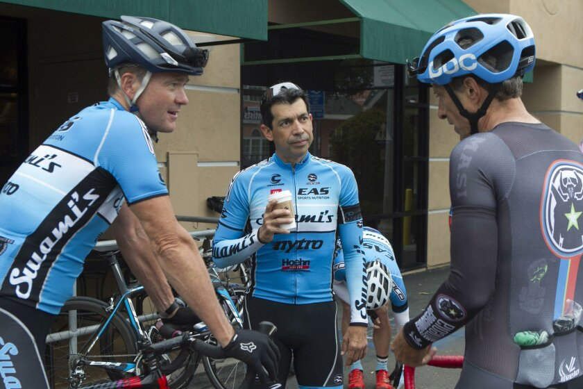 Troy Huerta (center), an avid cyclist in North County, rides every Wednesday with an elite group of cyclists. Here he chats with Lee Crane (left) and Andy McClure before the ride.